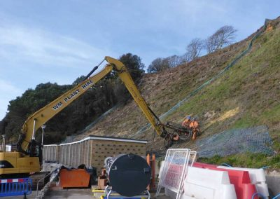 Long reach excavator mounted drill rig being used to drill lower rows of hollow bar soil nails