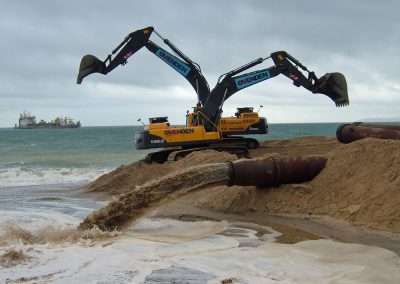 Sand is pumped from the offshore dredger to the beach and retained by a 'bund'