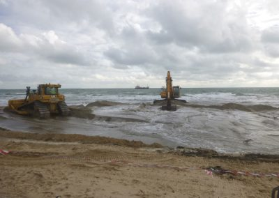 Sand is moved around in the bund while the water flows back out to sea
